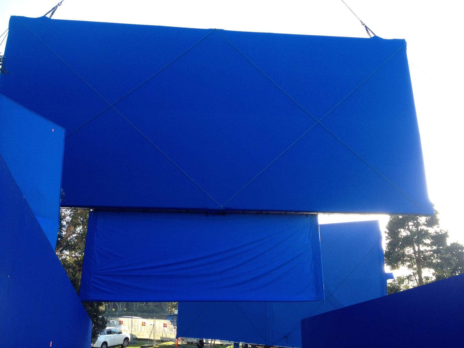 A cluster of blue screens on set outdoors
